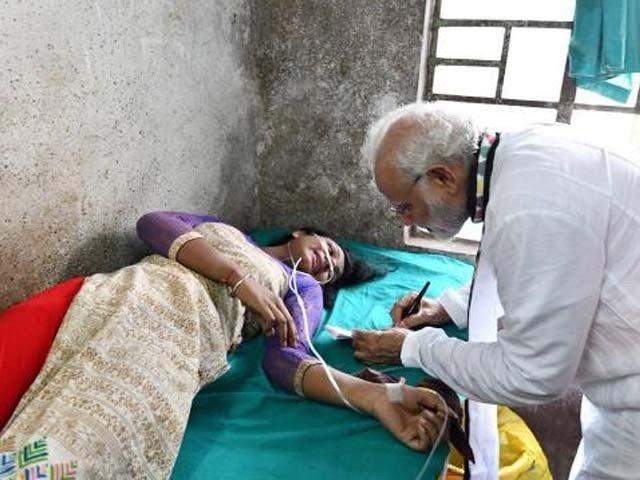 وزیراعظم مودی زخمی خاتون کارکن کو آٹو گراف دے رہے ہیں۔ فوٹو : بھارتی میڈیا